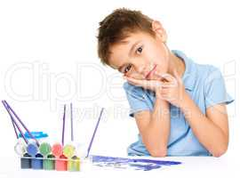 Young is daydreaming while drawing with paints