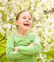 Portrait of a little girl near tree in bloom