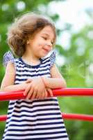 Cute little girl is playing in playground