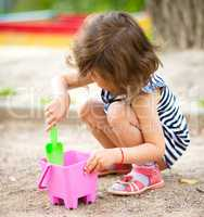 Little girl is playing with sand in playground