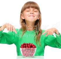 Cute girl is eating cherries