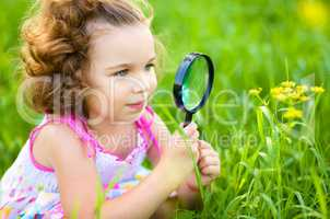 Young girl is looking at flower through magnifier