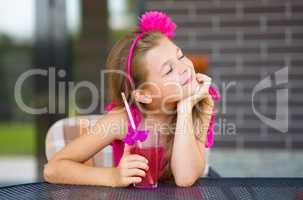 Little girl is drinking cherry juice