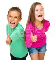 Little boy and girl are showing thumb up sign
