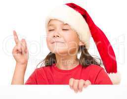 Little girl in santa hat is holding blank board