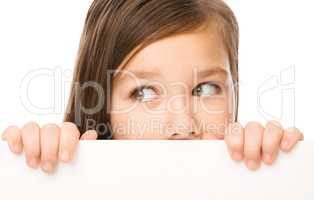 Little girl is looking from out blank board