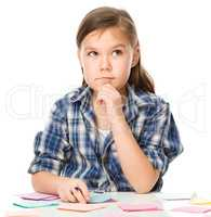 Girl is writing on color stickers using pen