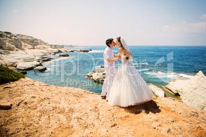 Elegant smiling bride and groom walking on the beach, kissing, wedding ceremony, Mediterranean Sea.