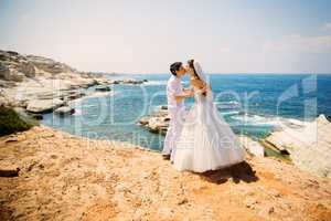 Elegant smiling bride and groom walking on the beach, kissing, wedding ceremony, Mediterranean Sea.