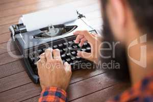 A man is typing on a type writer