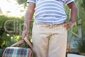 Child with hand on hips holding a bag