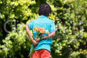 A kid hiding bouquet behind back
