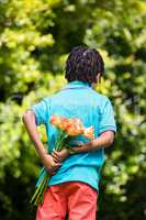 Rear view of a kid hiding bouquet behind back