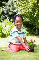 A boy sitting in the grass with plant
