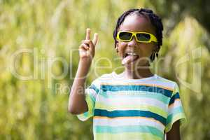 A kid with sunglasses making faces