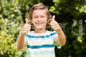 A little boy is putting up their thumbs in the air