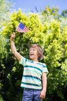A little boy is holding an american flag
