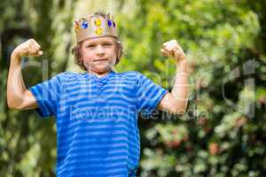 Cute boy with a crown showing his muscles