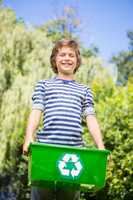 Low angle view of happy boy holding a recycling box