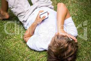 Child lying using a smartphone