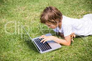 Child lying using a laptop