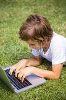 Child lying using a laptop
