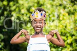 Cute mixed-race girl holding a crown and showing her biceps