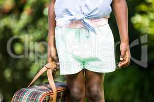 Close up of mixed-race girl holding a suitcase
