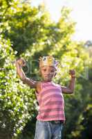 Boy putting arms up with crown