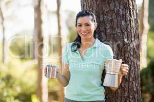 Woman smiling and holding a cup and a coffee maker