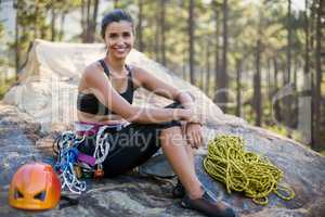 Woman smiling and sitting with climbing equipment