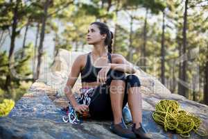 Woman sitting and posing with climbing equipment