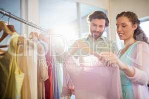 Woman showing shirt to man at shopping mall