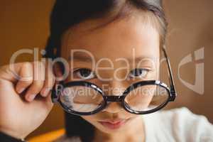 Schoolchild holding her glasses