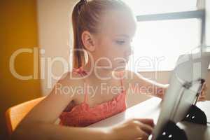 Seated girl using digital tablet