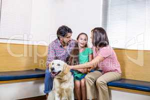 Family waiting on vet waiting room with their dog