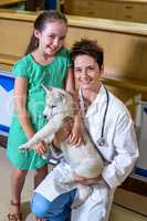 Portrait of little girl and woman vet holding a cute puppy