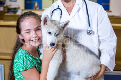 Portrait of little girl giving a hug to a puppy in vets arms
