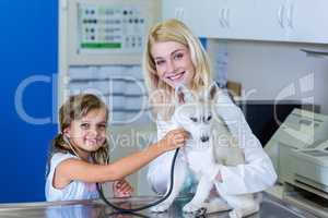 Little girl examining a puppy with a stethoscope with the woman