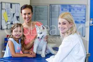 Woman vet and puppys owners smiling and posing