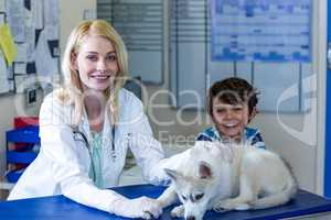 Woman vet and little boy smiling and posing with a cute puppy