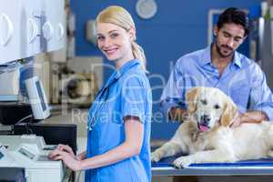 Woman vet smiling and posing in front of owner with his dog