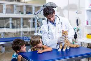 Vet taking care of a cat while two children are looking at the c