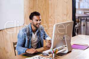 A young man writing notes at computer desk