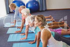 Seniors and fitness instructor stretching their legs