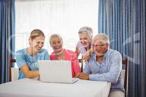 Seniors and woman using laptop