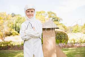 Portrait of cute boy with astronaut dress posing next to a rocke