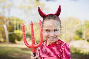 Portrait of cute girl pretending to be a devil