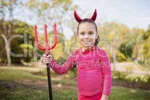 Portrait of cute girl smiling and posing with devil dress