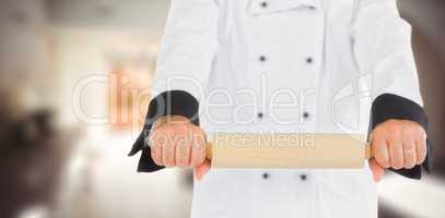 Composite image of close up on a chef holding a rolling pin